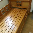 小さい棚付きの木製ベッド