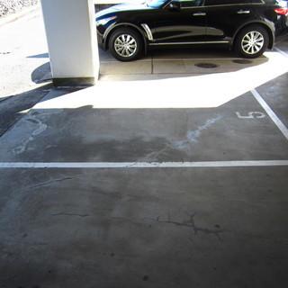 屋根付コンクリート舗装、両側が空地の駐車場です。