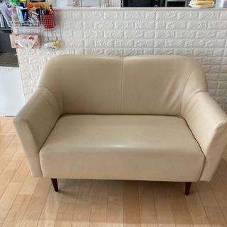 2人掛けクリーム色ソファーの画像